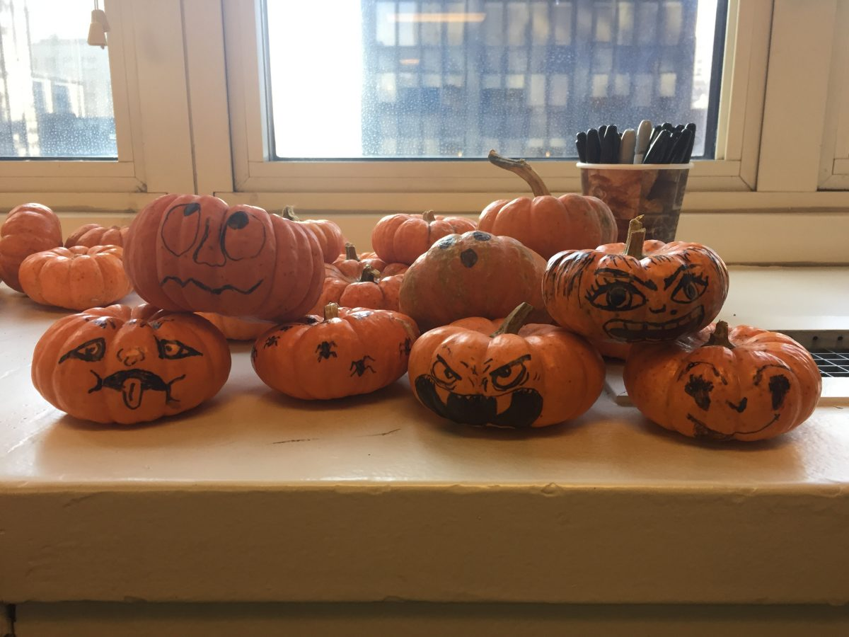 Mini pumpkins with faces drawn on them